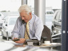 Car salesman sitting at desk, using telephone while making calculation