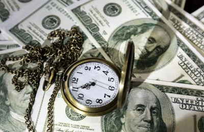 Pocket watch and dollar bills under dim light